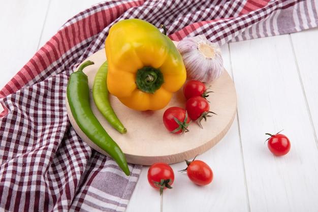 Seitenansicht von gemüse als knoblauch-tomaten-pfeffer auf schneidebrett auf kariertem stoff auf holz