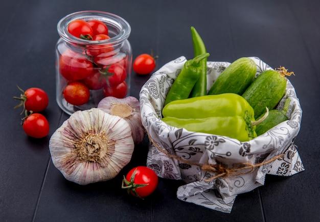 Seitenansicht von gemüse als korb von pfeffer und gurke und glas tomate mit knoblauch auf schwarz
