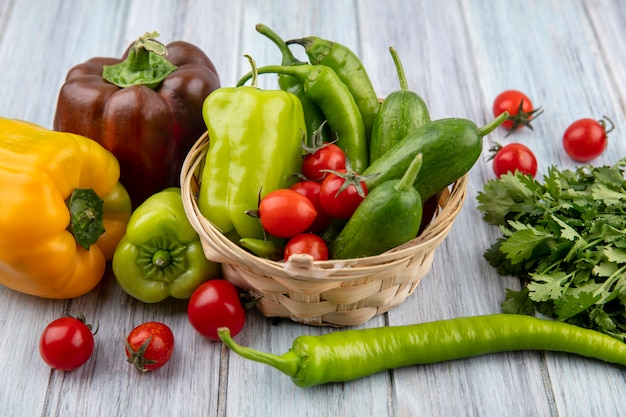 Seitenansicht von gemüse als pfeffer und gurke im korb mit koriander und tomaten herum auf holz