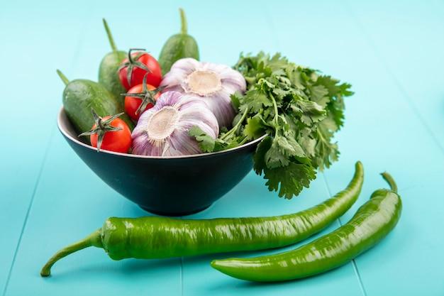 Seitenansicht von gemüse als tomatengurkenkoriander und knoblauch in schüssel mit paprika auf blau