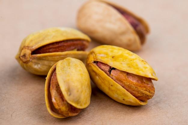 Seitenansicht von gesalzenen gerösteten pistazien auf altem papierbeschaffenheitshintergrund