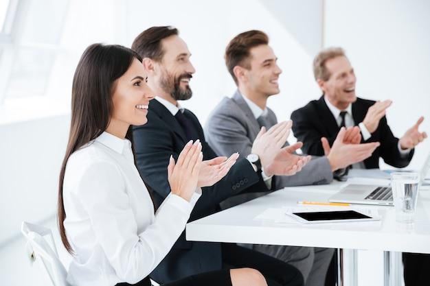 Seitenansicht von geschäftsleuten werden applaudiert und sitzen am tisch im büro