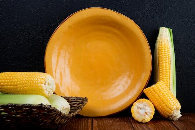 Seitenansicht von geschnittenen und ganzen maiskolben und leerem teller auf holzoberfläche und schwarzer oberfläche