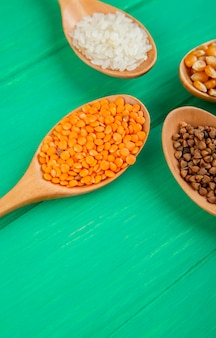 Seitenansicht von getreidekörnern und samen in holzlöffeln corns reis buchweizen und roten linsen auf grünem tisch