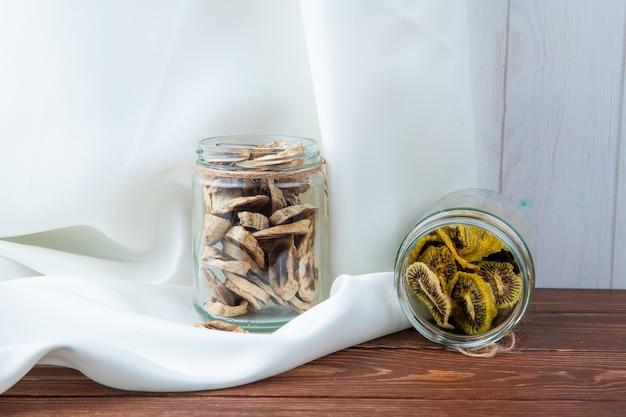 Seitenansicht von getrockneten bananenchips mit getrockneten kiwischnitten in gläsern auf weißem hintergrund
