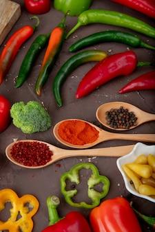 Seitenansicht von gewürzlöffeln mit brokkoli und paprika auf kastanienbraunem hintergrund