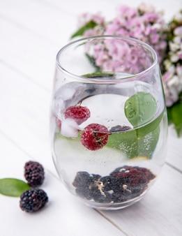 Seitenansicht von glas wasser mit himbeeren und brombeeren auf einer weißen oberfläche