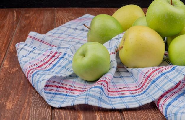 Seitenansicht von grünen und gelben äpfeln auf kariertem stoff und holzoberfläche