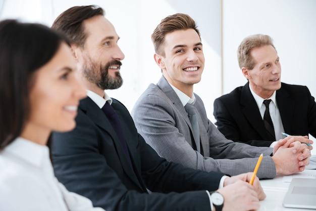 Seitenansicht von happy business-leute sitzen am tisch im büro und ein mann schaut in die kamera