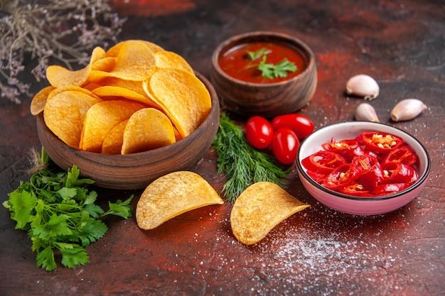 Seitenansicht von hausgemachten leckeren knusprigen kartoffelchips in einer kleinen braunen schüssel ölflasche grüne tomaten knoblauchketchup und gehackter pfeffer auf dunklem tisch