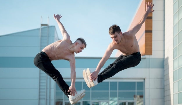 Seitenansicht von hemdlosen hip-hop-künstlern, die mitten in der luft tanzen