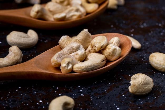 Seitenansicht von holzlöffeln mit cashewnüssen auf schwarzem hintergrund