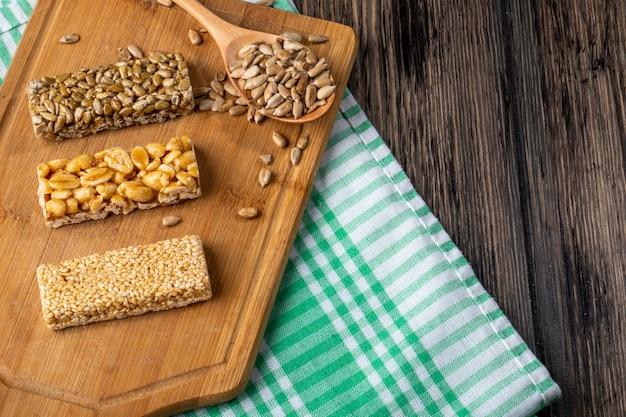 Seitenansicht von honigriegeln mit erdnusssesam und sonnenblumenkernen auf einem holzbrett auf rustikalem