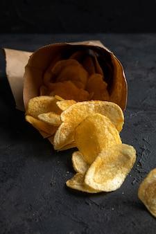 Seitenansicht von kartoffelchips, die von einem pfeffersack auf schwarz verstreut sind