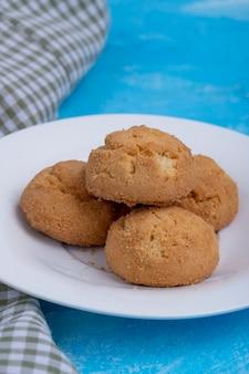Seitenansicht von keksen auf einem weißen teller auf blau