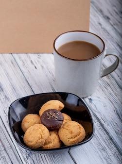 Seitenansicht von keksen in einer schwarzen schüssel und einer tasse mit kakao auf holz