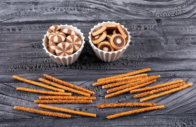 Seitenansicht von keksen in schalen und crackern auf dunkler horizontaler