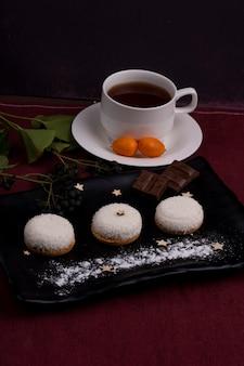 Seitenansicht von keksen mit kokosnussflocken-schokoladenstücken auf einer schwarzen tafel, die mit tee auf dunkelheit serviert wird