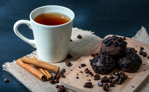 Seitenansicht von keksen und schokolade auf schneidebrett mit tasse tee und zimt auf sackleinen und blauem hintergrund