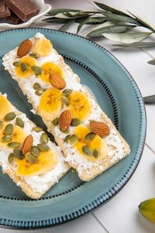 Seitenansicht von knusprigen crackern mit frischkäse, bananen-, mandel- und kürbiskernen auf einem teller auf weißem holz