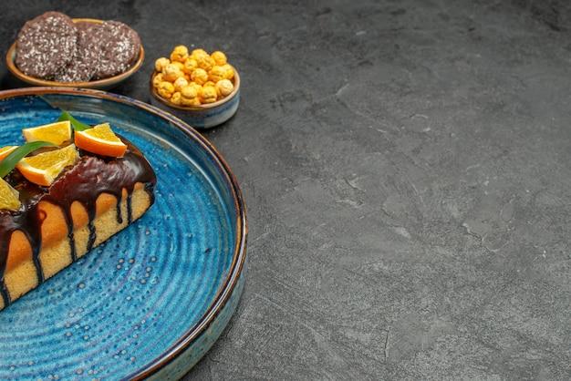 Seitenansicht von köstlichen kuchen auf blauem tablett und keksen auf dunklem tisch