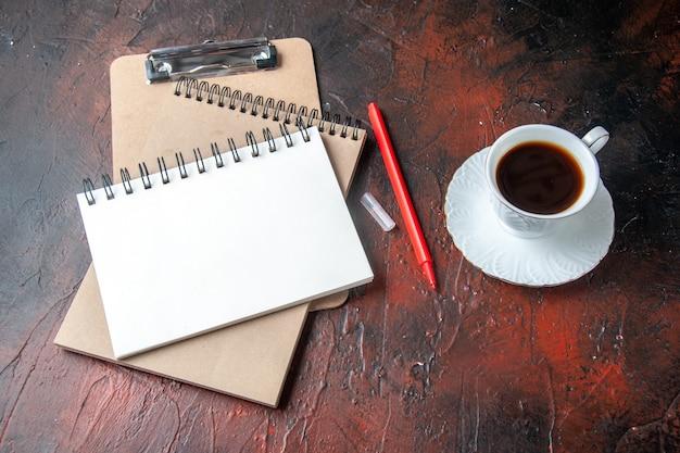 Seitenansicht von kraft-spiral-notizbüchern mit stift und einer tasse tee auf dunklem hintergrund