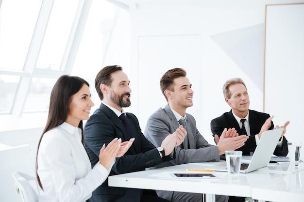 Seitenansicht von lächelnden geschäftsleuten, die am tisch sitzen und im konferenzraum applaudieren