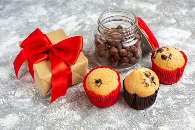 Seitenansicht von leckeren kleinen cupcakes und schokolade in einem glastopf neben einem weihnachtsgeschenk mit rotem band auf eisfläche