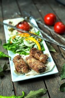 Seitenansicht von lula kebab mit zwiebelkräutern gegrilltem gemüse und spießen