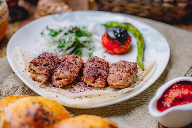 Seitenansicht von lula kebab mit zwiebelkräutern sumakh und gegrilltem gemüse auf lavash in einem weißen teller