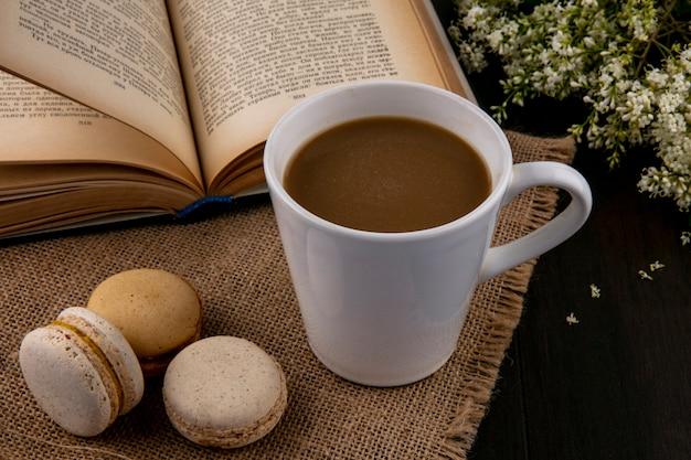 Seitenansicht von macarons mit einer tasse kaffee auf einer beigen serviette mit einem offenen buch und blumen auf einer schwarzen oberfläche