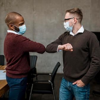Seitenansicht von männern, die sich während eines treffens gegenseitig grüßen und medizinische masken tragen