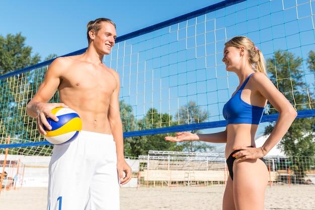 Seitenansicht von männlichen und weiblichen volleyballspielern, die ein gespräch durch das netz haben