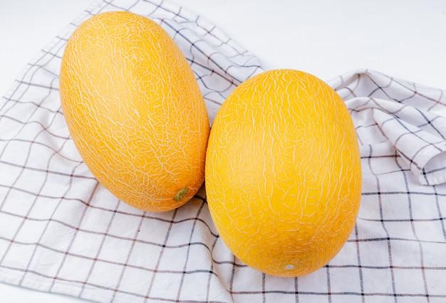 Seitenansicht von melonen auf kariertem stoffhintergrund