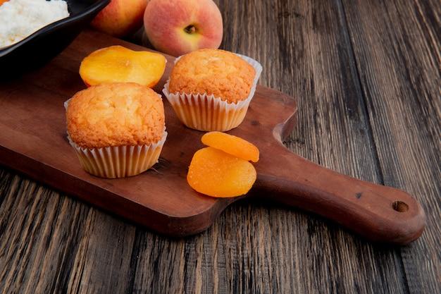 Seitenansicht von muffins mit getrockneten aprikosen auf holzschneidebrett und frischen pfirsichen auf rustikalem
