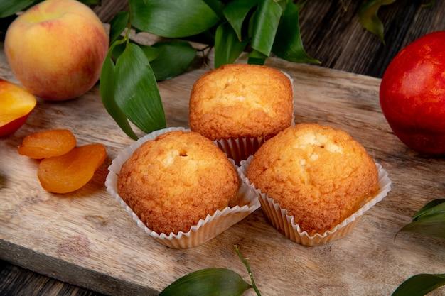 Seitenansicht von muffins mit getrockneten aprikosen und frischen pfirsichen auf holzbrett auf rustikalem tisch