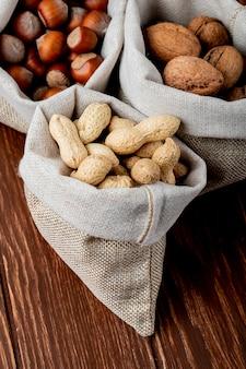Seitenansicht von nüssen in säcken walnüssen erdnüssen und haselnüssen in der schale auf hölzernem hintergrund