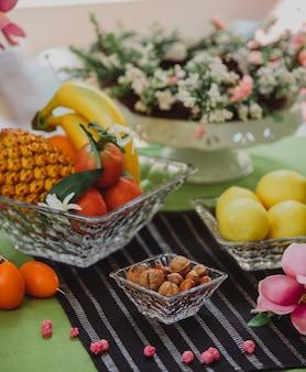 Seitenansicht von nüssen und früchten in den ziervasen auf dem tisch