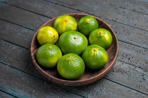 Seitenansicht von oben grün-gelbe limetten grün-gelbe limetten in braunem teller auf dem tisch