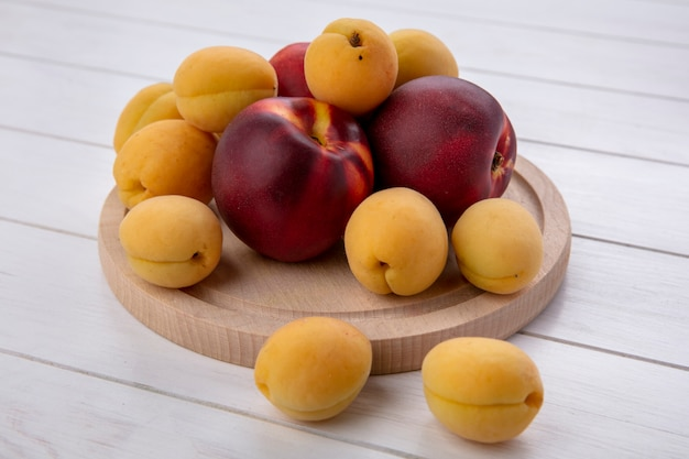Seitenansicht von pfirsichen mit aprikosen auf einem ständer auf einer weißen oberfläche