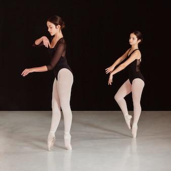 Seitenansicht von professionellen balletttänzern, die zusammen in spitzenschuhen üben