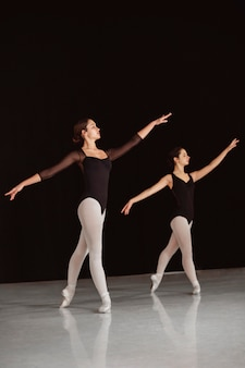 Seitenansicht von professionellen balletttänzern in trikots, die in spitzenschuhen tanzen