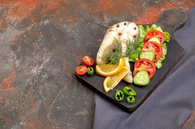 Seitenansicht von rohen fischen und pfefferfrischen nahrungsmitteln auf schwarzem schneidebrett auf dunklem handtuch auf gemischter farboberfläche