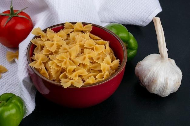 Seitenansicht von rohen nudeln in einer schüssel mit tomaten knoblauch und paprika auf einem weißen handtuch auf einer schwarzen oberfläche