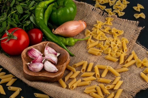 Seitenansicht von rohen nudeln mit tomaten knoblauch und bulgarian und chilischoten auf einer beigen serviette