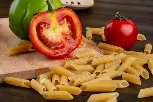 Seitenansicht von rohen nudeln mit tomaten und paprika auf einem schneidebrett auf einer holzoberfläche