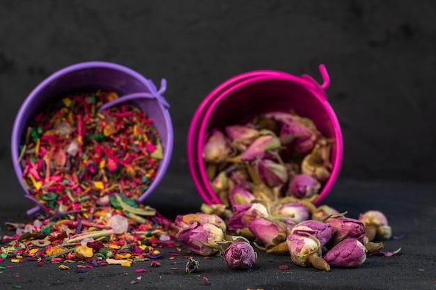 Seitenansicht von rosentee und trockenen blütenblättern verstreut von kleinen eimern auf schwarz