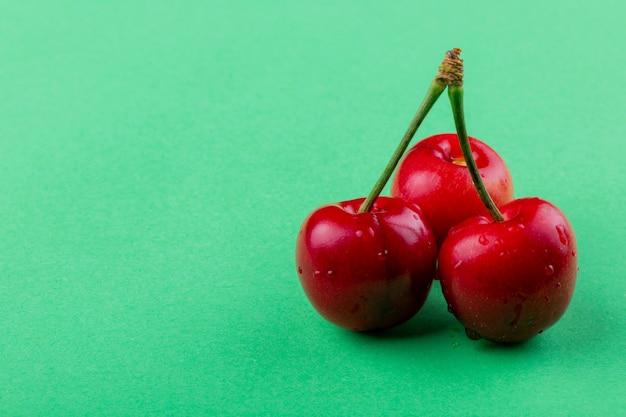 Seitenansicht von roten reifen kirschen mit wassertropfen lokalisiert auf grün mit kopienraum