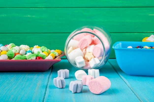 Seitenansicht von schalen mit verschiedenen bunten bonbons und marshmallow, die von einem glasglas auf blauem hintergrund verstreut werden