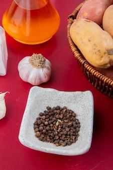 Seitenansicht von schwarzen pfeffersamen und knoblauch mit geschmolzener butter und kartoffeln im korb auf bordo